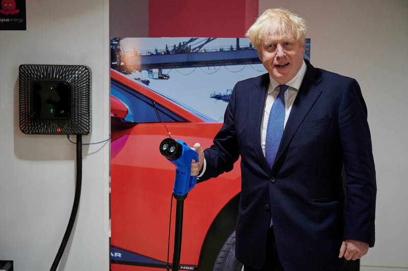 Britain's Prime Minister Boris Johnson holds an electric vehicle charging cable as he visits the headquarters of Octopus Energy, in London, Britain October 5, 2020. Leon Neal/Pool via REUTERS