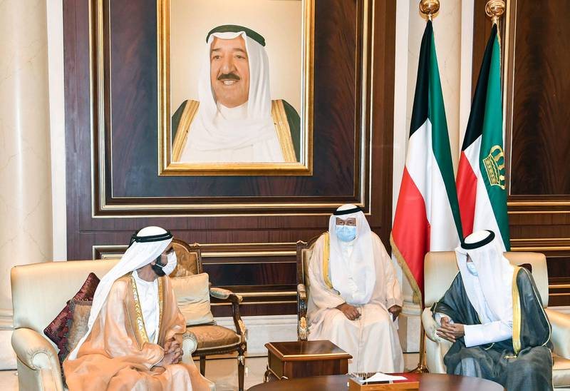 """A handout picture released by the press office of the Emir of Kuwait Diwan on October 4, 2020 shows UAE Vice President and Prime Minister and ruler of Dubai Sheikh Mohammed bin Rashid al-Maktoum (L) meeting with Kuwait's new Emir Sheikh Nawaf al-Ahmad al-Jaber Al-Sabah (R) and offering condolences to the latter, while mask-clad due to the COVID-19 coronavirus pandemic, at the Emiri Terminal of Kuwait International Airport.  - == RESTRICTED TO EDITORIAL USE - MANDATORY CREDIT """"AFP PHOTO / HO / EMIR OF KUWAIT DIWAN"""" - NO MARKETING NO ADVERTISING CAMPAIGNS - DISTRIBUTED AS A SERVICE TO CLIENTS ==  / AFP / EMIR OF KUWAIT DIWAN / - / == RESTRICTED TO EDITORIAL USE - MANDATORY CREDIT """"AFP PHOTO / HO / EMIR OF KUWAIT DIWAN"""" - NO MARKETING NO ADVERTISING CAMPAIGNS - DISTRIBUTED AS A SERVICE TO CLIENTS =="""