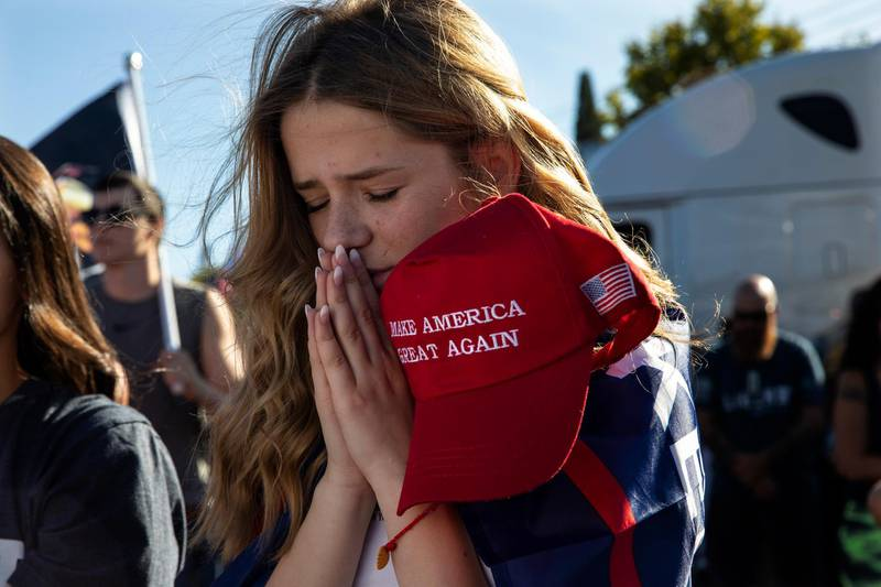 Liza Durasenko, 16, from Oregon City, Ore., prays during a rally in support of President Donald Trump on Saturday, Aug. 29, 2020, in Clackamas, Ore. (AP Photo/Paula Bronstein)