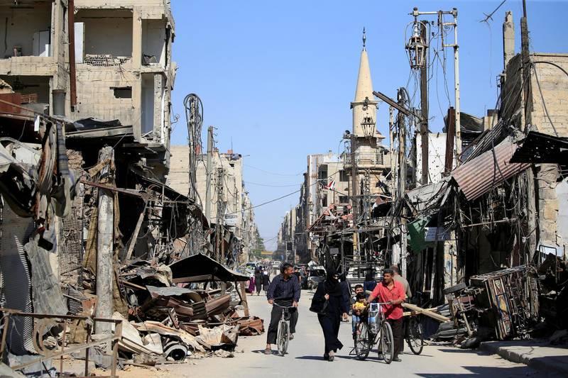 FILE PHOTO: People walk in a street during a media tour in Douma near Damascus, Syria April 23, 2018. REUTERS/ Ali Hashisho/File Photo