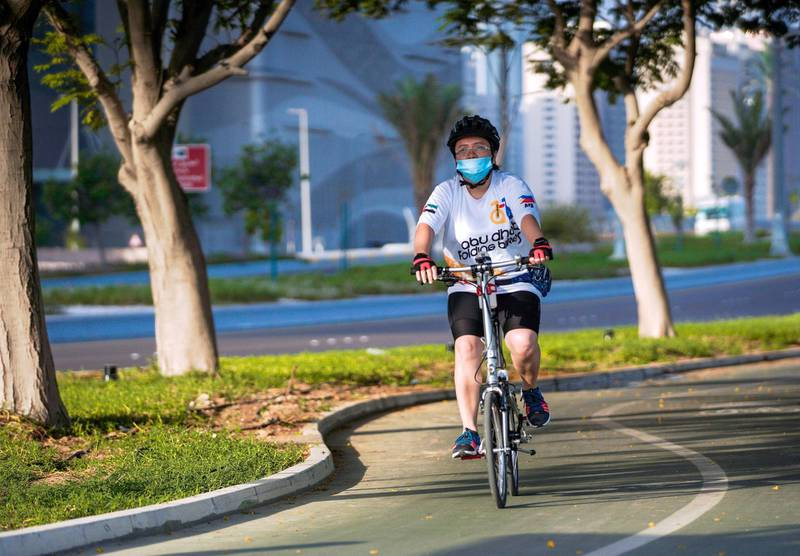Abu Dhabi, United Arab Emirates, July 11, 2020.     A cyclist on the bike pathway along the Corniche with a face mask on during the Covid-19 pandemic.Victor Besa  / The NationalSection:  StandaloneReporter: