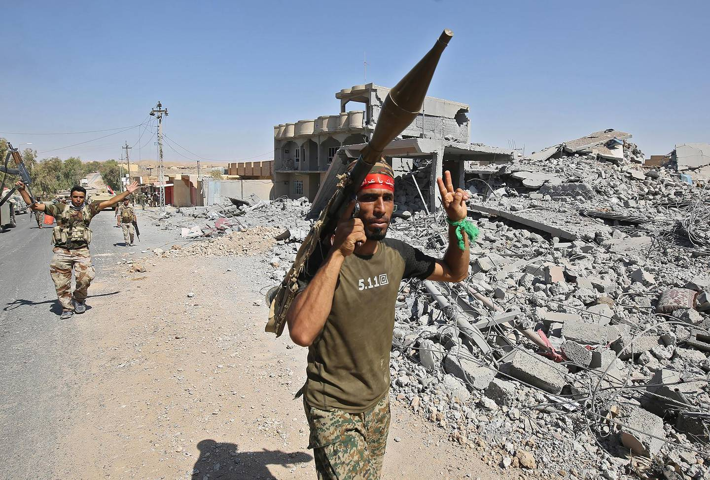 A fighter of the Hashed Al-Shaabi (Popular Mobilization units) flashes the victory gesture while carrying a rocket-propelled grenade (RPG) launcher during the advance through the town of Tal Afar, west of Mosul, after the Iraqi government announced the launch of the operation to retake it from Islamic State (IS) group control, on August 26, 2017. (Photo by AHMAD AL-RUBAYE / AFP)