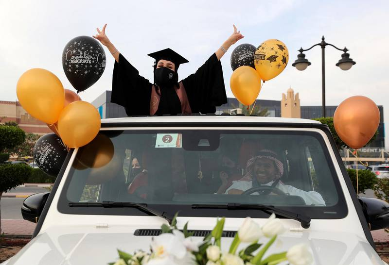Ajman, United Arab Emirates - Reporter: Anam Rizvi. News. Andalus Abdulwahhab celebrates out the sunroof of her car before her drive through graduation from Ajman University because of Covid-19. Wednesday, February 10th, 2021. Ajman. Chris Whiteoak / The National