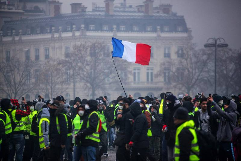 """TOPSHOT - Demonstrators gather near the Arc de Triomphe as a French flag floats during a protest of Yellow vests (Gilets jaunes) against rising oil prices and living costs, on December 1, 2018 in Paris.  Anti-government protesters torched dozens of cars and set fire to storefronts during daylong clashes with riot police across central Paris on December 1, as thousands took part in fresh """"yellow vest"""" protests against high fuel taxes. / AFP / -"""