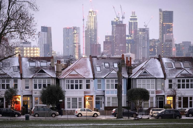 Snow-covered roofs and the glowing lights in the porches of south London Edwardian homes and residential high-rise towers under construction, on 8th February 2021, in London, England. (Photo by Richard Baker / In Pictures via Getty Images)