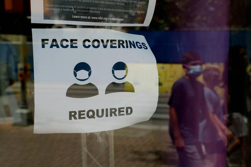 A visitor wearing a masks to protect against the spread of COVID-19 passes a sign requiring masks, Tuesday, July 7, 2020, in San Antonio. Texas Gov. Greg Abbott has declared masks or face coverings must be worn in public across most of the state as local officials across the state say their hospitals are becoming increasingly stretched and are in danger of becoming overrun as cases of the coronavirus surge. (AP Photo/Eric Gay)