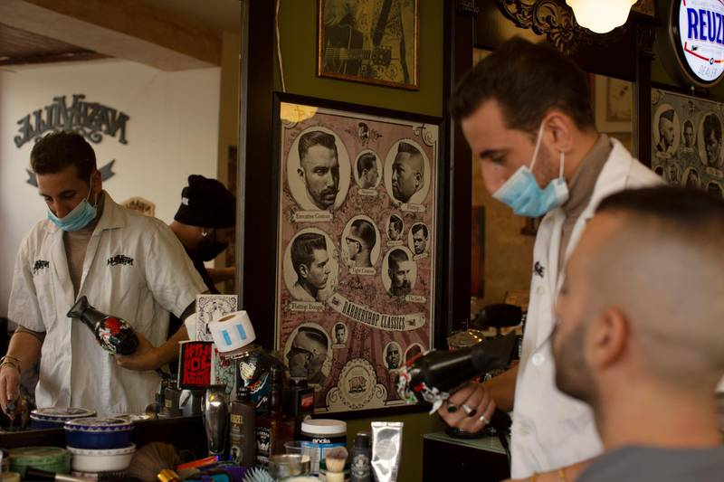 A barber gives a customer a haircut after coronavirus restrictions were eased, opening shopping centers, gyms, barber shops, among other sites in Jerusalem, Tuesday, Feb. 23, 2021. (AP Photo/Maya Alleruzzo)