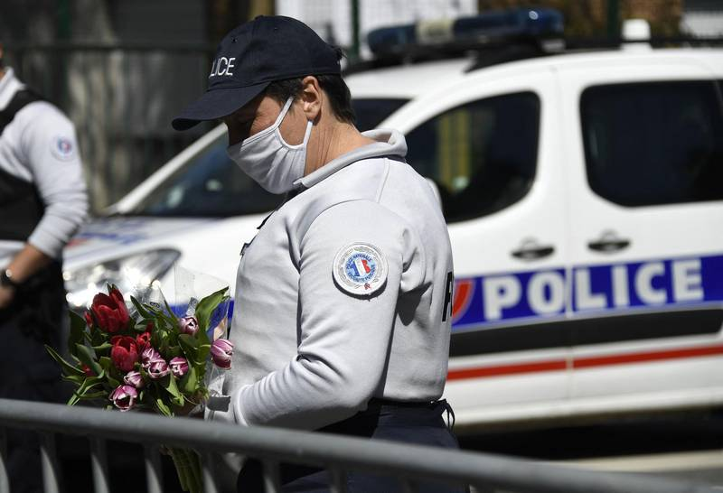 A Police officer holds flowers brought by people, to be taken down to the police station where a police official was stabbed death Friday, in Rambouillet, south-west of Paris, on April 25, 2021. French prosectors opened a terror probe after a woman working for the police was stabbed to death in Rambouillet, a well-heeled usually peaceful commuter town about 60 kilometres (40 miles) from Paris. The attack revived the trauma of a spate of deadly attacks last year in France blamed on Islamist radicals. / AFP / Bertrand GUAY