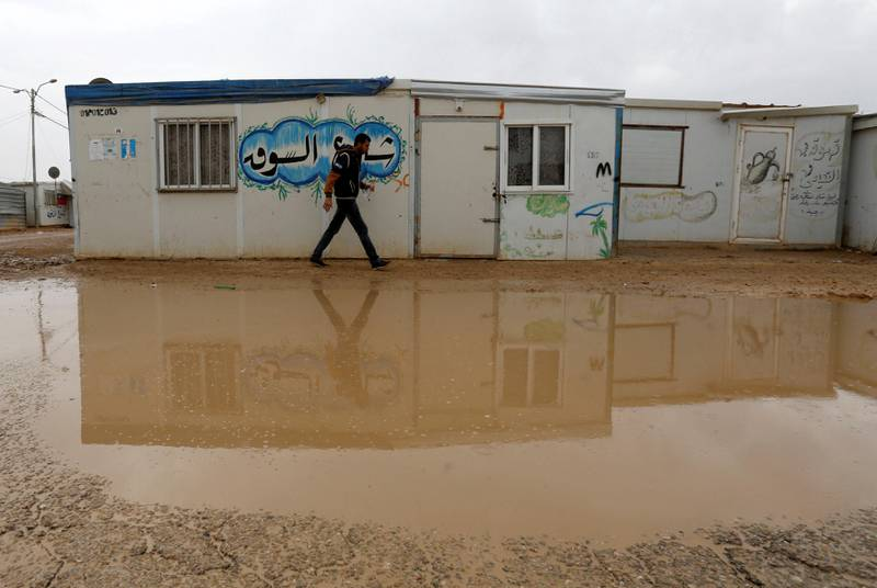 A Syrian refugee walks during rainy weather at the Al Zaatari refugee camp in the Jordanian city of Mafraq, near the border with Syria December 18, 2016. REUTERS/Muhammad Hamed - RTX2VJDU