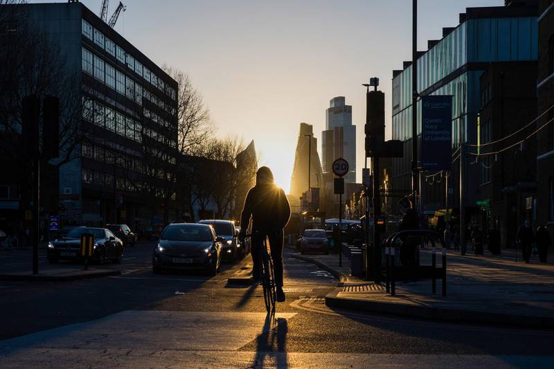 A cyclist on the Mile End Road against a backdrop of skyscrapers in the City of London square mile financial district in London, U.K., on Thursday, Feb. 18, 2021. Amsterdamovertook London as Europe's largest share trading center in January after Brexit saw about half of the city's volumes move to the continent. Photographer: Chris Ratcliffe/Bloomberg