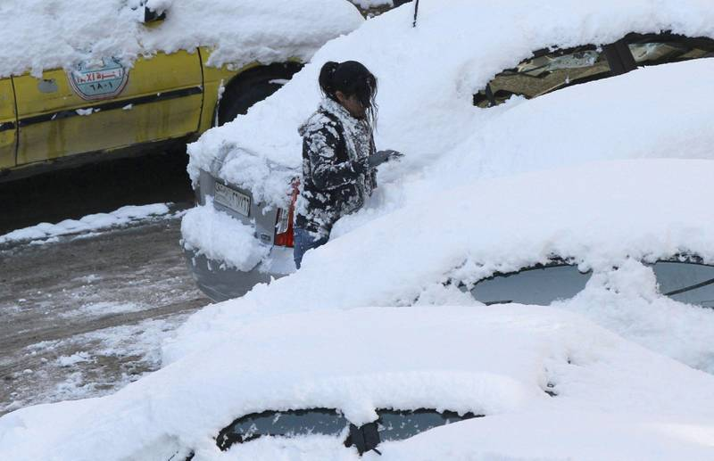 A woman removes snow from a car on January 10, 2013 in the Syrian capital of Damascus after heavy snow falls. Snow carpeted Syria's war-torn cities but sparked no let-up in the fighting, instead heaping fresh misery on a civilian population already enduring a chronic shortage of heating fuel and daily power cuts.  AFP PHOTO   / LOUAI BESHARA