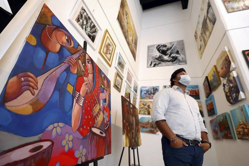 Dubai, United Arab Emirates - Reporter: N/A. News. Covid-19/Coronavirus. A gentleman looks at the paintings at Anyahh popular art with Covid-19 precautions. Saturday, October 10th, 2020. Dubai. Chris Whiteoak / The National