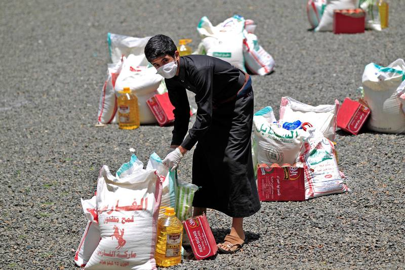 A Yemeni youth carries a portion of food aid, distributed by Yadon Tabney development foundation, in Yemen's capital Sanaa on May 17, 2020. (Photo by MOHAMMED HUWAIS / AFP)