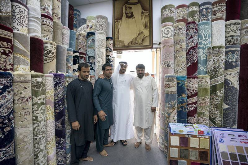 ABU DHABI, UNITED ARAB EMIRATES -  February 22, 2018: HH Sheikh Mohamed bin Zayed Al Nahyan, Crown Prince of Abu Dhabi and Deputy Supreme Commander of the UAE Armed Forces (3rd L), stands for a photograph with staff at Al Safa Carpet shop, in the carpet market of the Mina Zayed Port.  ( Ryan Carter for the Crown Prince Court - Abu Dhabi ) ---