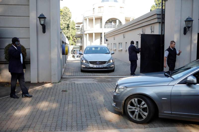 Private security personnel man the gate to the compound of the controversial business family Gupta in Johannesburg while cars belonging to the the Hawks, The Directorate for Priority Crime Investigation, are stationed outside, in Johannesburg, South Africa, on February 14, 2018.  South African President Zuma's battle to stay in office despite the ruling ANC party reportedly asking him to step down is the latest in a long history of career controversies. Zuma has been involved in several scandals, one known as Guptagate. It involved the president's allegedly corrupt relationship with a wealthy family of Indian immigrants headed by three brothers -- Ajay, Atul and Rajesh Gupta -- who built a business empire in mining, media, technology and engineering. / AFP PHOTO / WIKUS DE WET