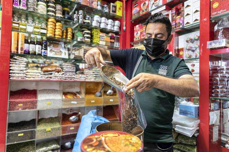 """DUBAI, UNITED ARAB EMIRATES. 25 FEBRUARY 2021. COVID - 19 Standalone. Deira souk during the time of Covid. Shop keeper Jalil Ghirban Arshru, fills a bag of tea destined to be sold to tourists. """"It's been very tough, with almost no business, and the tourists mainly not coming."""" (Photo: Antonie Robertson/The National) Journalist: Nick Webster. Section: National."""