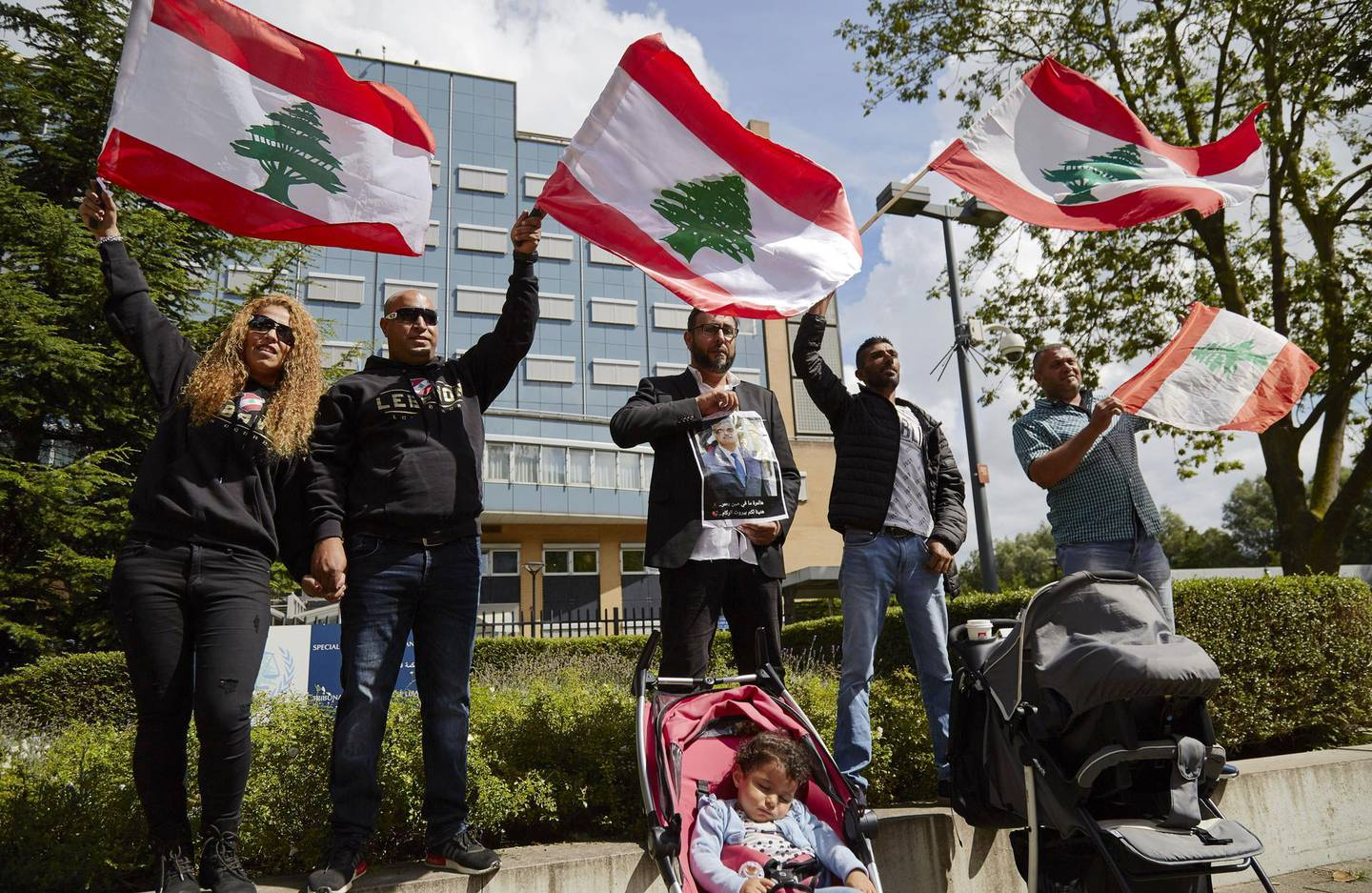 THE HAGUE, NETHERLANDS - AUGUST 18: Supporters of former Prime Minister Rafiq Hariri wave Lebanese flags outside the Lebanon Tribunal on August 18, 2020 in The Hague, Netherlands. The Special Tribunal for Lebanon must render its verdict on the trial of four men accused of participating in the 2005 assassination of former Lebanese Prime Minister Rafic Hariri. (Photo by Pierre Crom/Getty Images)