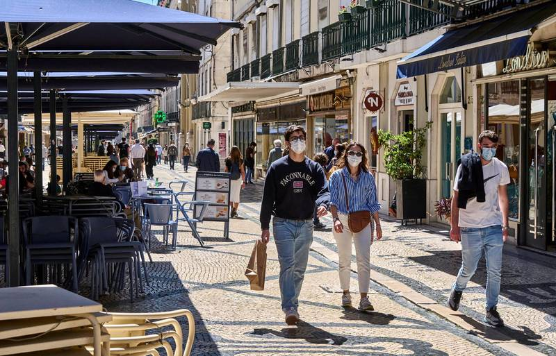LISBON, PORTUGAL - APRIL 17: People wearing protective masks walk past piled up restaurant tables and chairs on a sunny afternoon in Rua Augusta during the COVID-19 Coronavirus pandemic on April 17, 2021 in Lisbon, Portugal. According to updated data from the General Direction of Health (DGS) Portugal confirmed a total of 829,911 infections and 16,937 deaths since the beginning of the pandemic. The government has relaxed confinement measures and renewed the country's state of emergency until April 30. (Photo by Horacio Villalobos#Corbis/Corbis via Getty Images)