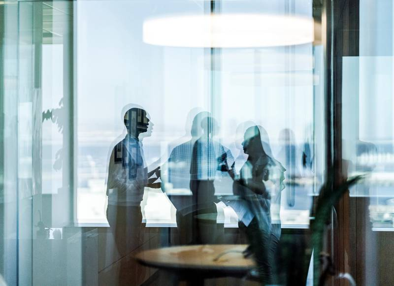 Business colleagues seen through glass. Professionals are discussing in meeting. They are standing at workplace.