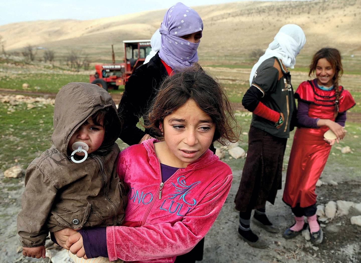 SINJAR, IRAQ - DECEMBER 20: Yezidis, fled from Islamic State of Iraq and Levant (ISIL) forces' attacks on their home town Sinjar, stay in harsh conditions as the winter starts, in a valley of western Sinjar Mountain in Sinjar district of Mosul, Irak on December 20, 2014. Yezidi women and children are seen out side of the tents. (Photo by Emrah Yorulmaz/Anadolu Agency/Getty Images)