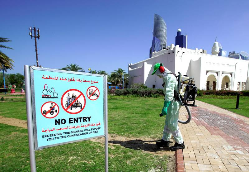 Abu Dhabi, United Arab Emirates, March 25, 2020.   Standalone:A Tadweer sanitary worker sprays the Family Park at the Corniche with disinfectants to counter the spread of the coronavirus.Victor Besa / The NationalSection:  NAReporter: