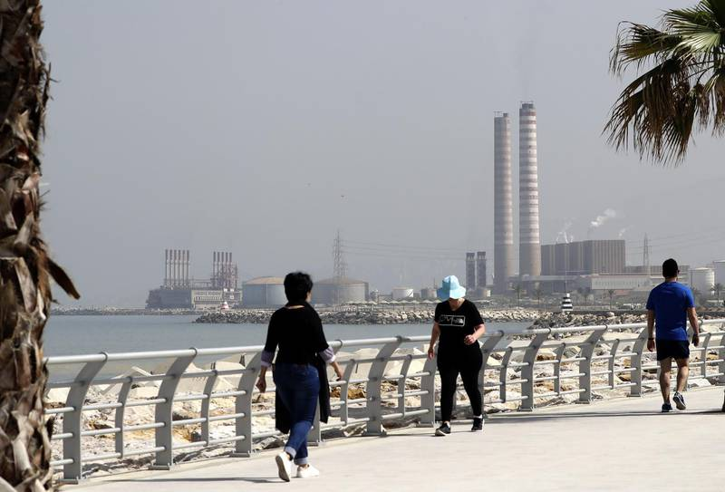 People walk on the seaside promenade with the floating Turkish power station Karadeniz Powership Fatmagul (L) seen in the background next to Lebanon's Zouk Mosbeh power plant, north of the capital Beirut, on April 9, 2019. The Lebanese cabinet has approved a plan to restructure the country's ailing electricity sector vowing to provide power 24 hours a day from a grid notorious for blackouts. / AFP / JOSEPH EID