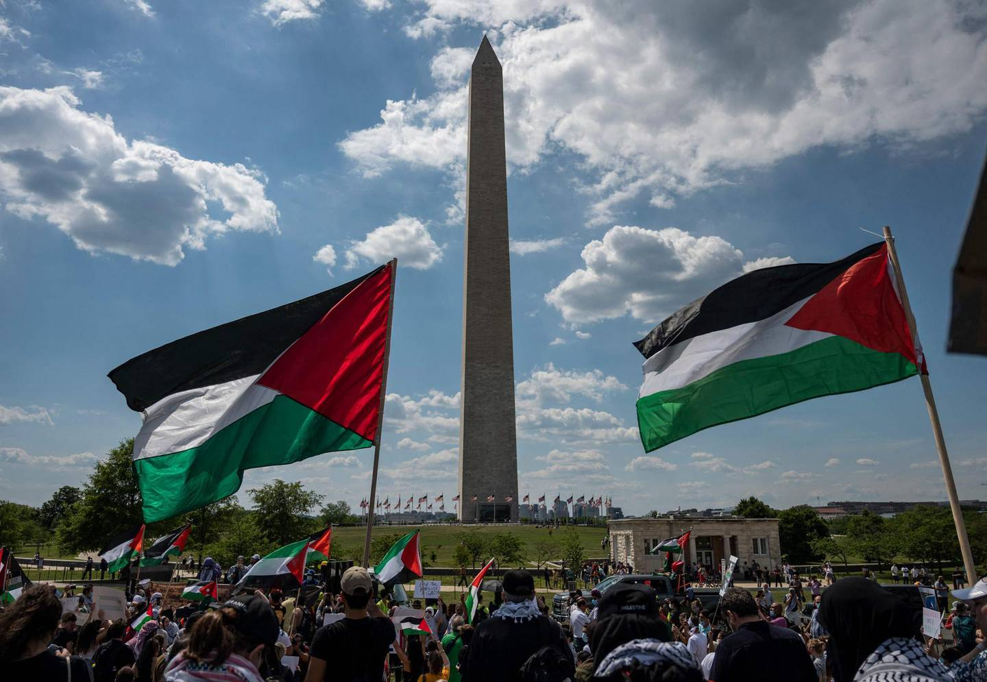 """Activists and protesters march in support of Palestine near the Washington monument in Washington, DC on May 15, 2021. US President Joe Biden, in a phone call with Israeli Prime Minister Benjamin Netanyahu, expressed his """"grave concern"""" Saturday over the flareup of violence in Israel and Gaza, the White House announced.  / AFP / ANDREW CABALLERO-REYNOLDS"""