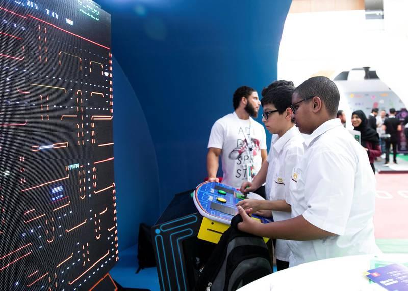 DUBAI, UNITED ARAB EMIRATES. 06 OCTOBER 2019. Schoolboys play pacman at Dubai Internet City booth at Gitex Technology Week at Dubai World Trade Center.(Photo: Reem Mohammed/The National)Reporter:Section: