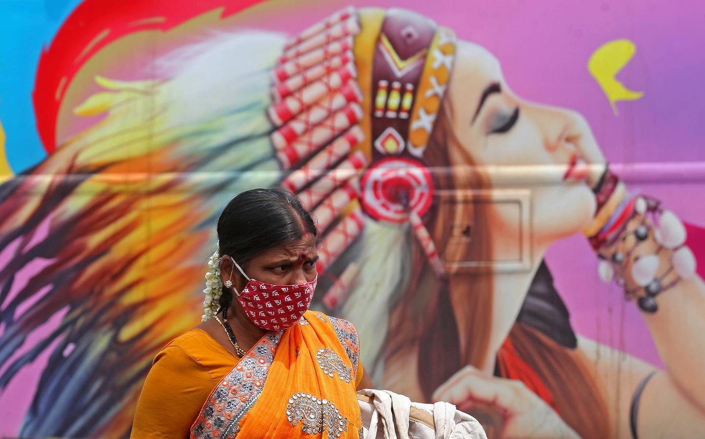 epa09121992 A woman wears a mask in Bangalore, India, 08 April 2021. India recorded massive surge of 126,315 Covid-19 cases is the highest single-day spike in COVID-19 infections. India is seeing a second wave of the virus which has led several states including Maharashtra and the capital, New Delhi, to impose new restrictions.  EPA/JAGADEESH NV