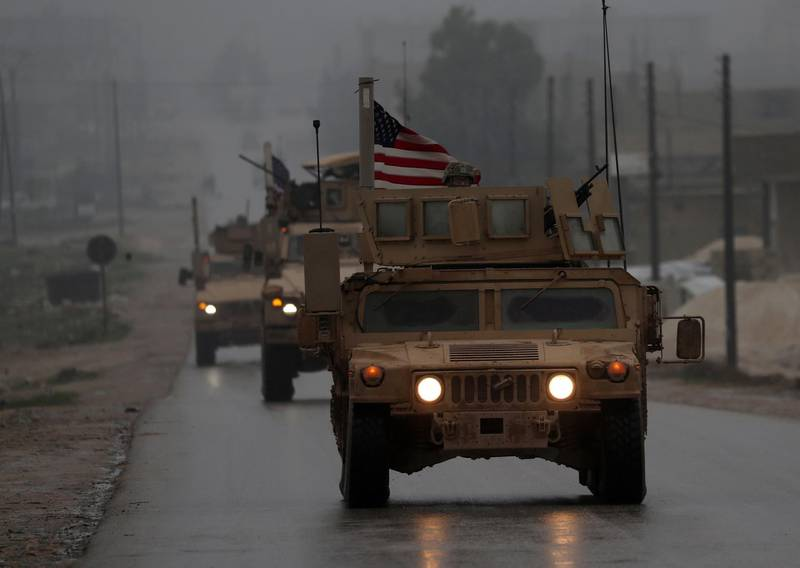 """(FILES) In this file photo taken on December 30, 2018, shows a line of US military vehicles in Syria's northern city of Manbij.  President Donald Trump appeared to backtrack on December 31, 2018 on shock plans for an immediate pullout of US troops from Syria, but said his drive to end American involvement in wars made him a """"hero."""" The shift came a day after a senior Republican senator said Trump had promised to stay in Syria to finish the job of defeating the Islamic State group, also known as ISIS. / AFP / Delil SOULEIMAN"""