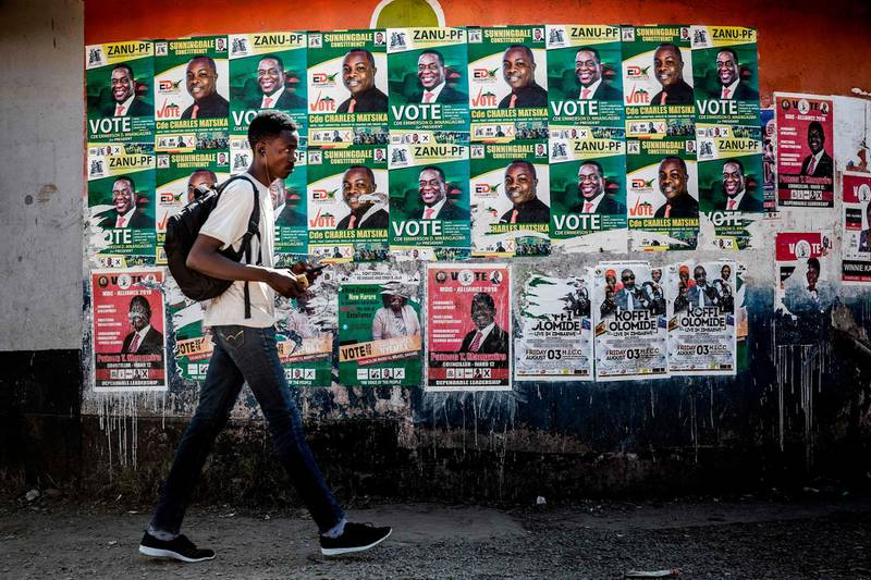 A man walks in front of electoral posters in a market at the suburb of Mbare in Zimbabwe's capital Harare on July 27, 2018, prior to the upcoming July 30, presidential election.  Mbare is a high-density suburb and one of the poorest areas of Harare and was known for being a former president Robert Mugabe's stronghold. The former president was ousted in November 2017, and his successor Emmerson Mnangagwa has promised a free vote, inviting back previously banned observers in an effort to show a renewed commitment to democracy. / AFP / Luis TATO