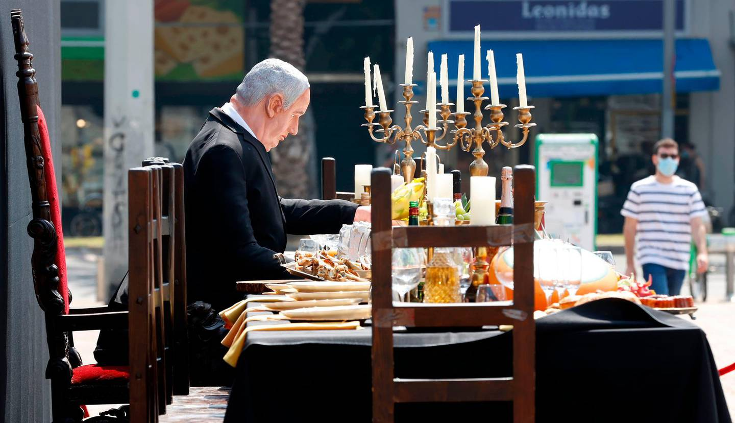 """A doll depicting Israeli Prime Minister Benjamin Netanyahu sits on a table simulating the """"Last Supper"""" during a protest performance by Israeli artist Itay Zalait on July 29, 2020 at Rabin Square in Tel Aviv as protests demanding Netanyahu's resignation are growing by the week. / AFP / JACK GUEZ"""