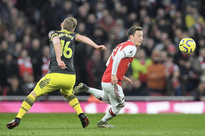 Arsenal's German midfielder Mesut Ozil (R) vies with Southampton's English midfielder James Ward-Prowse (L) during the English Premier League football match between Arsenal and Southampton at the Emirates Stadium in London on November 23, 2019. (Photo by Daniel LEAL-OLIVAS / AFP) / RESTRICTED TO EDITORIAL USE. No use with unauthorized audio, video, data, fixture lists, club/league logos or 'live' services. Online in-match use limited to 120 images. An additional 40 images may be used in extra time. No video emulation. Social media in-match use limited to 120 images. An additional 40 images may be used in extra time. No use in betting publications, games or single club/league/player publications. /