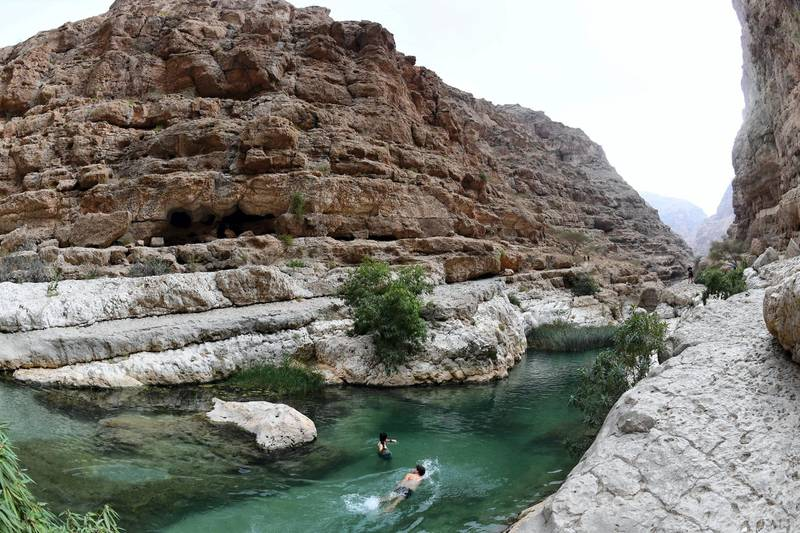 Tourists swim at Wadi Shab in the Sharqiyah region near the Omani capital Muscat on November 27, 2018. (Photo by GIUSEPPE CACACE / AFP)