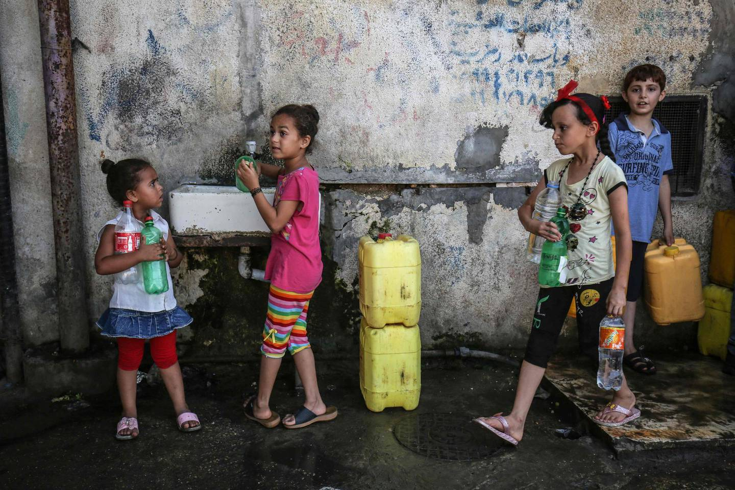 Palestinian children fill jerricans with drinking water from public taps at a refugee camp in Rafah in the southern Gaza Strip on July 30, 2019. An internal ethics report has alleged mismanagement and abuses of authority at the highest levels of the UN agency for Palestinian refugees even as the organisation faced an unprecedented crisis after US funding cuts. Lacking natural resources, the Gaza Strip suffers from a chronic shortage of water, electricity and petrol. More than two-thirds of the population depends on humanitarian aid. / AFP / SAID KHATIB