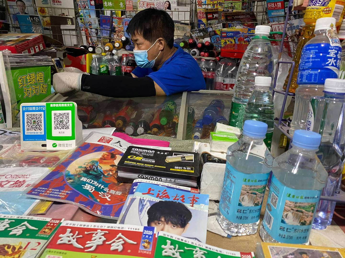 A news-stand vendor, wearing a mask to protect against the coronavirus, sits near QR codes for Alipay and WeChat, two popular online payment system in Beijing, China on Tuesday, July 21, 2020. Ant Group, the financial technology arm of e-commerce giant Alibaba Group, on Tuesday, Aug. 25, 2020, filed for a dual-listing in Hong Kong and Shanghai, in what would likely be the world's largest initial public stock offering since the coronavirus pandemic began. (AP Photo/Ng Han Guan, File)
