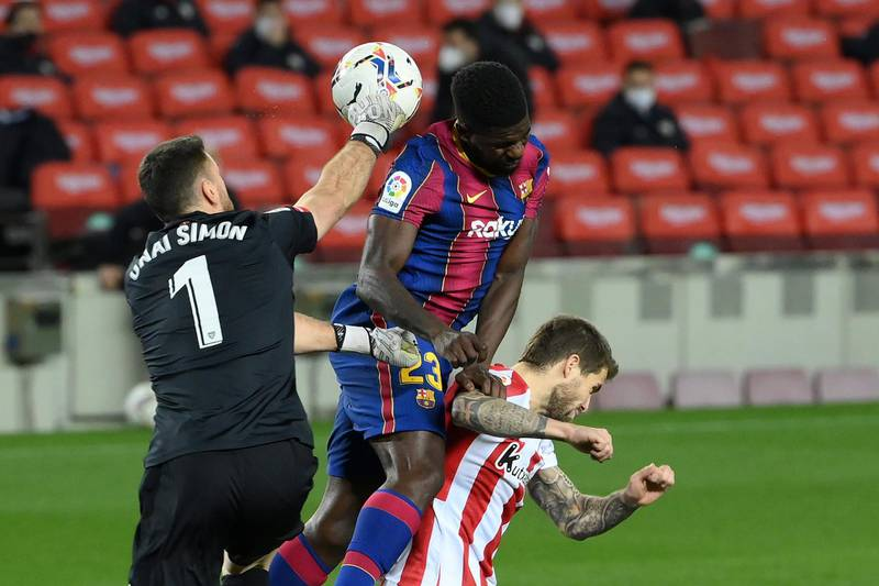 (FromL) Athletic Bilbao's Spanish goalkeeper Unai Simon, Barcelona's French defender Samuel Umtiti and Athletic Bilbao's Spanish defender Inigo Martinez jump for the ball during the Spanish league football match FC Barcelona against Athletic Club Bilbao at the Camp Nou stadium in Barcelona on January 31, 2021. (Photo by LLUIS GENE / AFP)