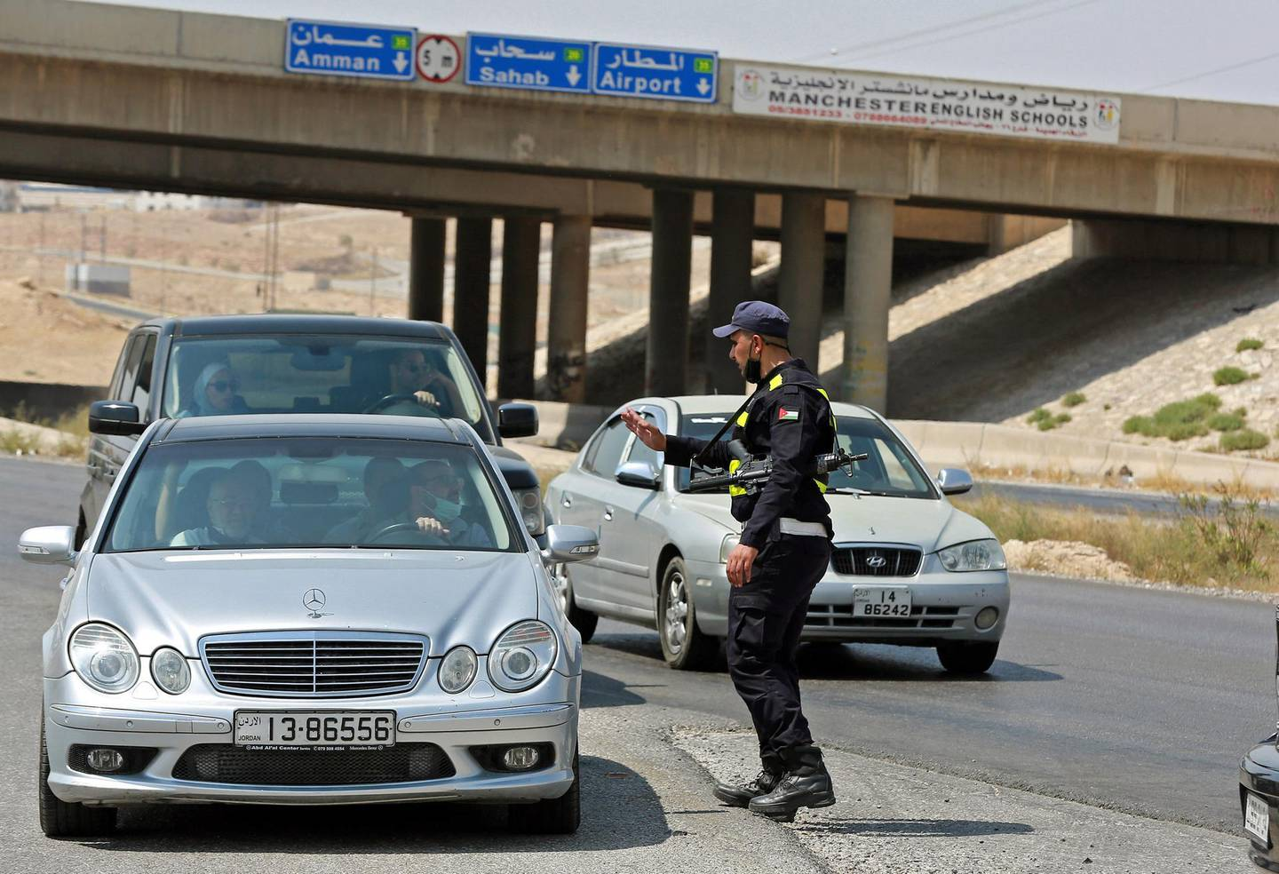 """A member of Jordanian security forces stops cars as the police and army close-off the area surrounding the site of an explosion at a military munitions depot in the city of Zarqa, 25 Km (15 miles) east of the capital Amman, on September 11, 2020. - A huge blast rocked a Jordanian military munitions depot early sparking a large fire, but the army said there were no casualties at the base situated in an uninhabited area, adding in a statement that the explosion was """"due to high temperatures provoking a chemical reaction in a shell"""". (Photo by Khalil MAZRAAWI / AFP)"""