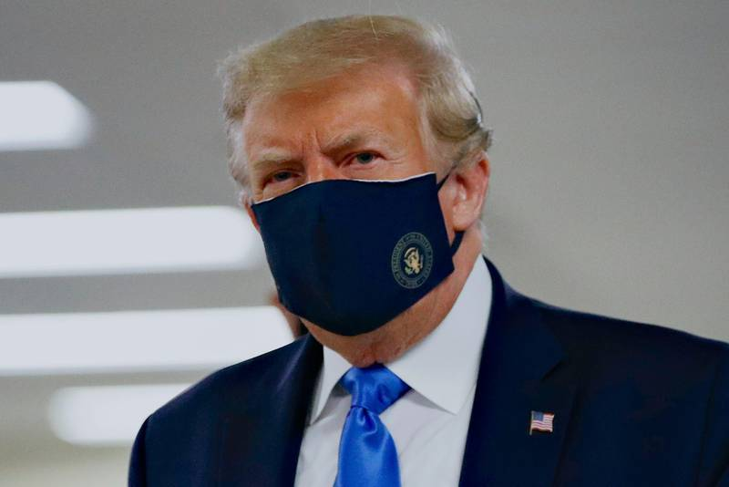 FILE - In this Saturday, July 11, 2020, file photo, President Donald Trump wears a face mask as he walks down a hallway during a visit to Walter Reed National Military Medical Center in Bethesda, Md. When Trump wore a mask publicly for the first time on Saturday,  he chose a navy-blue one that bore the presidential seal. It also matched the color of his suit. (AP Photo/Patrick Semansky, File)