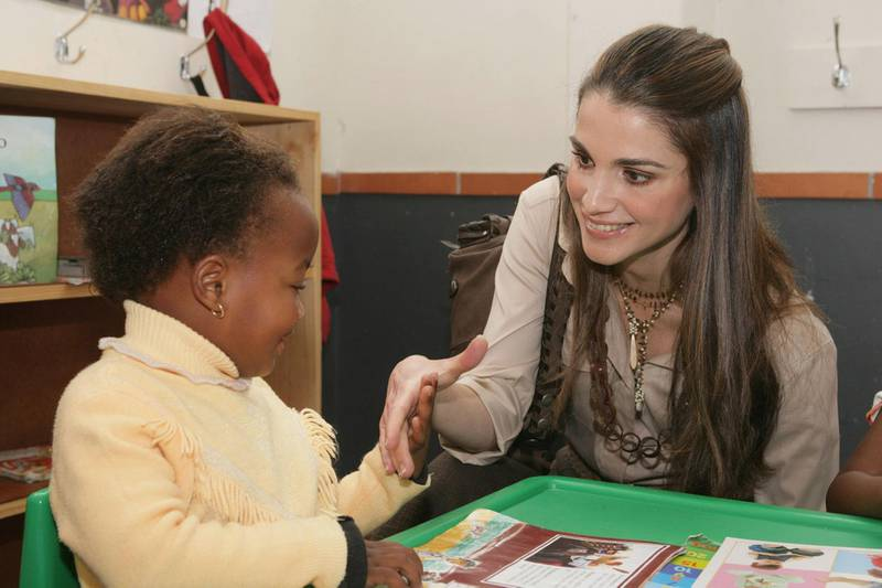 CAPE TOWN, SOUTH AFRICA - APRIL 03:  In this photo released by the Jordanian Royal Palace, Her Majesty Queen Rania of Jordan, a member of the UNICEF Global Leadership Initiative for Children, talks to a child during her visit to the Vukile Tshwete Enrichment Center in the city of Cape Town, South Africa April 03, 2006. (Photo by Jordanian Royal Court via Getty Images)