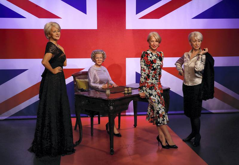 British actress Helen Mirren, (2R) poses with three waxwork models of herself, at the Madame Tussauds attraction in London on July 30, 2015. The models depict Mirren as herself attending a 'Red Carpet' event (L), playing the role of Britain's Queen Elizabeth II (2L) in the film 'The Queen', and as the character Jane Tennison from the television show 'Prime Suspect' (R).    AFP PHOTO / JUSTIN TALLIS (Photo by JUSTIN TALLIS / AFP)
