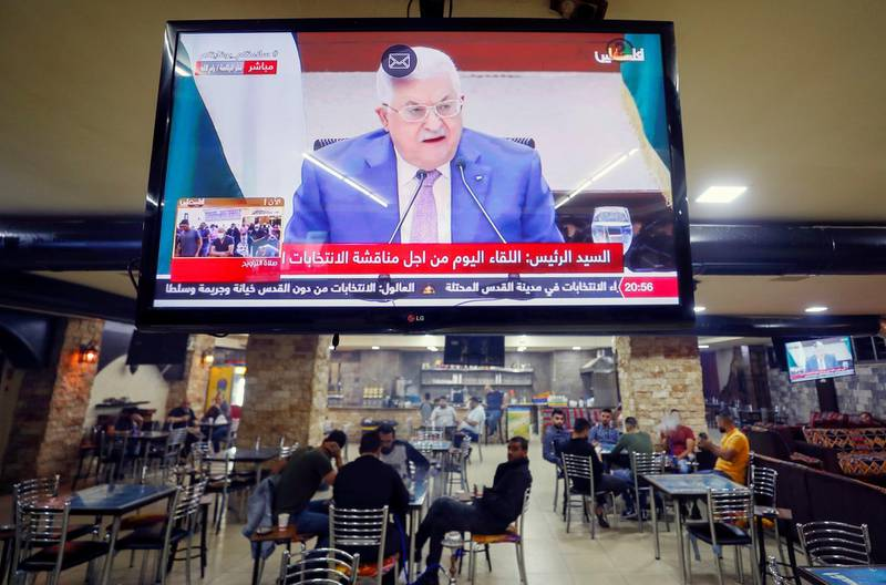 A screen displaying a live broadcast of Palestinian President Mahmoud Abbas's speech during a meeting to discuss upcoming elections, is seen in a coffee shop in Ramallah in the Israeli-occupied West Bank April 29, 2021. REUTERS/Mohamad Torokman