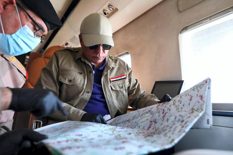 """A handout picture released by the Iraqi prime minister's media office on June 2, 2020 shows Iraq's new premier, Mustafa Kadhimi (R), looking at a map with a member of the security apparatus aboard a plane the flew him to the restive northern city of Kirkuk for an official visit, one month after Islamic State group jihadists claimed a suicide attack that wounded four people outside an intelligence headquarters in the multi-ethnic city. (Photo by - / IRAQI PRIME MINISTER'S PRESS OFFICE / AFP) / === RESTRICTED TO EDITORIAL USE - MANDATORY CREDIT """"AFP PHOTO / HO / IRAQI PRIME MINISTER'S PRESS OFFICE"""" - NO MARKETING NO ADVERTISING CAMPAIGNS - DISTRIBUTED AS A SERVICE TO CLIENTS ==="""