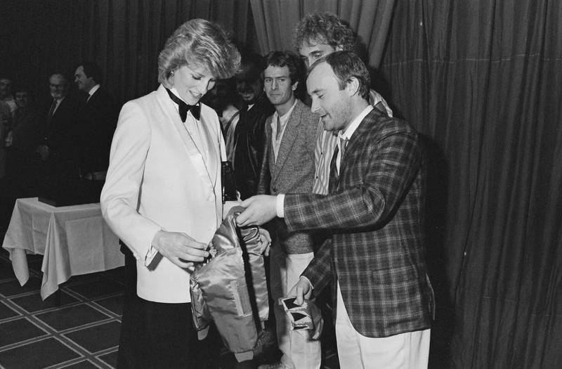 Diana, Princess of Wales (1961 - 1997) accepts a jacket with an embroidered gold crown for Prince William from British singer and drummer Phil Collins of rock band Genesis, before the band gave a Royal charity concert at the National Exhibition Centre, Birmingham, UK, 2nd March 1984. (Photo by Steve Wood/Daily Express/Hulton Archive/Getty Images)