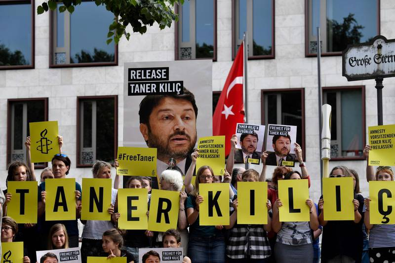 """(FILES) This file photo taken on June 15, 2017 shows Amnesty International activists holding  a portrait of the head of Amnesty International in Turkey, as they stage a protest against his detention in Turkey, in front of the Turkish Embassy in Berlin. An Istanbul court on January 31, 2018 ordered the conditional release of Taner Kilic, the head of Amnesty International in Turkey. A total of 11 activists including Kilic went on trial in Istanbul on terror charges which the rights watchdog said were """"baseless allegations"""".   / AFP PHOTO / John MACDOUGALL"""