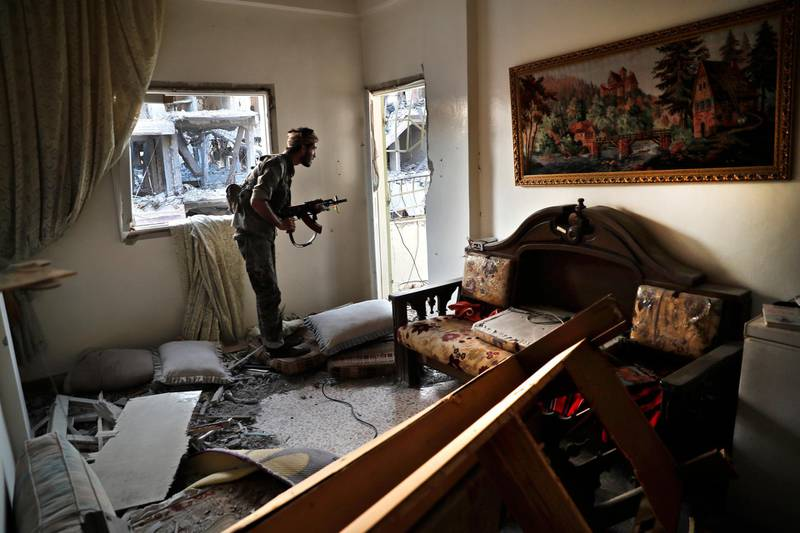 """FILE - In this July 27, 2017 file photo, a U.S.-backed Syrian Democratic Forces fighter looks through a window as he takes his position inside a destroyed apartment on the front line, in Raqqa, Syria. Amnesty International, an international rights group, urged the U.S.-led military coalition battling the Islamic State group to investigate airstrikes that killed civilians in the campaign to liberate the Syrian city of Raqqa from the extremists. Amnesty said Tuesday, Aug. 7, 2018,  that the U.S.-coalition's admission last month that it killed 78 more civilians than previously reported in the 2017 assault on Raqqa was just the """"tip of the iceberg."""" (AP Photo/Hussein Malla, File)"""