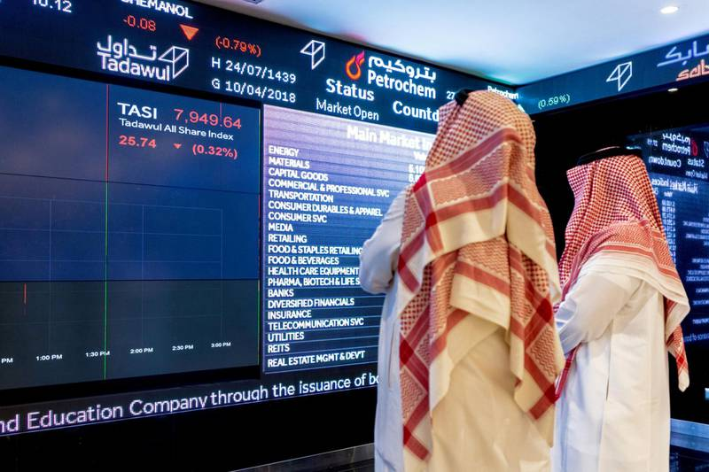Visitors look at stock price information displayed on a digital screen inside the Saudi Stock Exchange, also known as the Tadawul, in Riyadh, Saudi Arabia, on Tuesday, April 10, 2018. Foreign investors bought more Saudi stocks in March than ever before in anticipation of the kingdom's upgrade to emerging-market status. Photographer: Abdulrahman Abdullah/Bloomberg