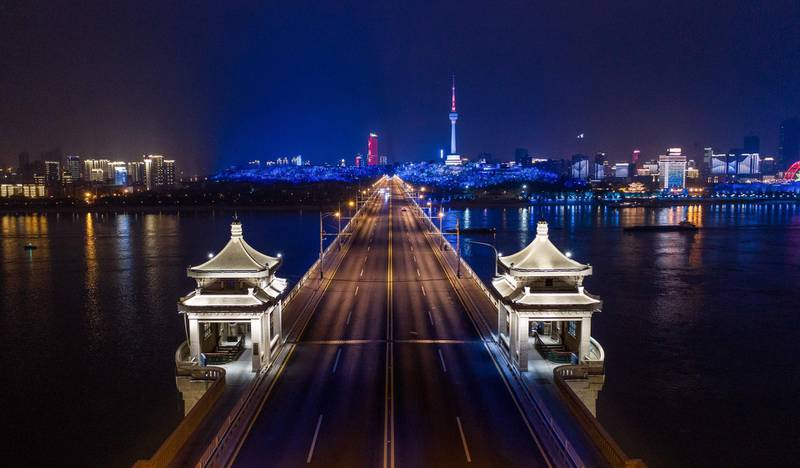 TOPSHOT - This aerial photo taken on March 16, 2020 shows a view of the Wuhan Yangtze River Bridge at night in Wuhan in China's central Hubei province. China reported on March 17 just one new domestic coronavirus infection but found 20 more cases imported from abroad, threatening to spoil its progress against the disease. - China OUT  / AFP / STR