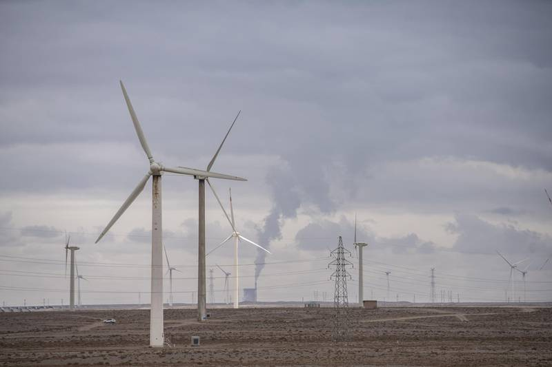 """Wind turbines in front of a coal-fired power plant on the outskirts of the new city area of Yumen, Gansu province, China, on Wednesday, March 31, 2021. Yumen, """"the cradle of China's oil industry,"""" has become a totem for China's changes over the past four decades—from a time of sacrifice and ideology to one of entrepreneurs and the pursuit of wealth, from the old economy to the new, from fossil fuels to renewable energy. Photographer: Qilai Shen/Bloomberg"""
