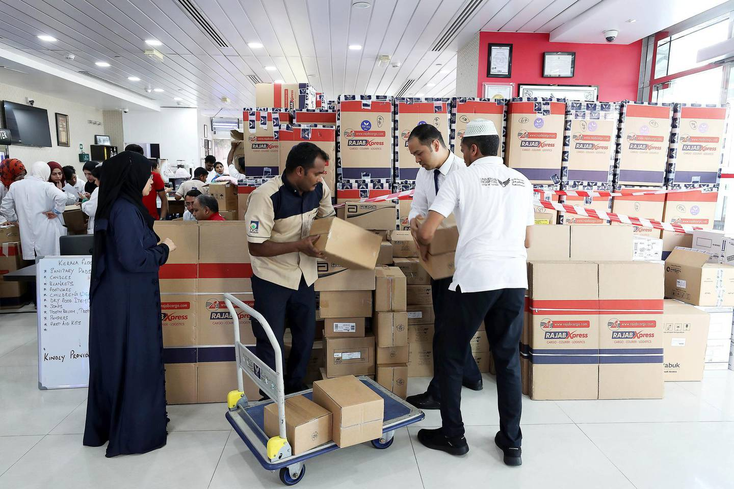 ABU DHABI, UNITED ARAB EMIRATES, August 19 – 2018 : Members of the Universal Rescue Team packing essential items such as slippers, clothes , food , medicines , blankets, baby items and other stuff in the aid boxes for the Kerala flood victims at the Universal Hospital in Abu Dhabi. ( Pawan Singh / The National )  For News. Story by John Dennehy
